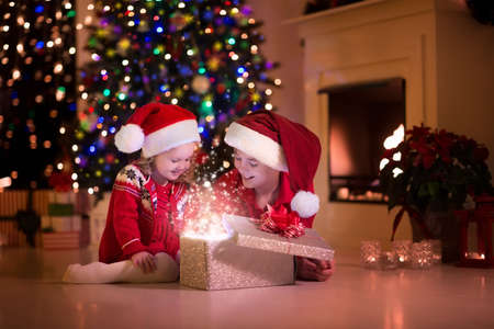Photo pour Family on Christmas eve at fireplace. Kids opening Xmas presents. Children under Christmas tree with gift boxes. Decorated living room with traditional fire place. Cozy warm winter evening at home. - image libre de droit