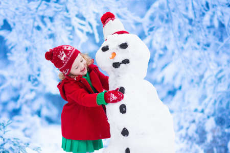 Foto de Funny little toddler girl in a red knitted Nordic hat and warm coat playing with a snow. Kids play outdoors in winter. Children having fun at Christmas time. Child building snowman at Xmas. - Imagen libre de derechos