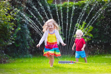 Photo pour Child playing with garden sprinkler. Preschooler kid running and jumping. Summer outdoor water fun in the backyard. Children play with hose watering flowers. Kids run and splash on hot sunny day. - image libre de droit