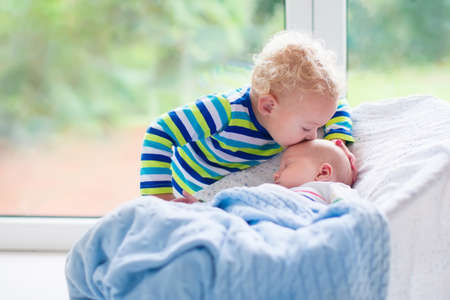 Foto de Cute little boy kissing his newborn brother. Toddler kid meeting new born sibling. Infant sleeping in white bouncer under a blanket. Kids playing and bonding. Children with small age difference. - Imagen libre de derechos