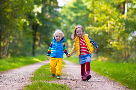 Foto de Kids playing in autumn park. Children play outdoors on a sunny fall day. Boy and girl running together hand in hand in a forest. Toddler and preschooler pick colorful oak leaf. Family fun outdoor - Imagen libre de derechos