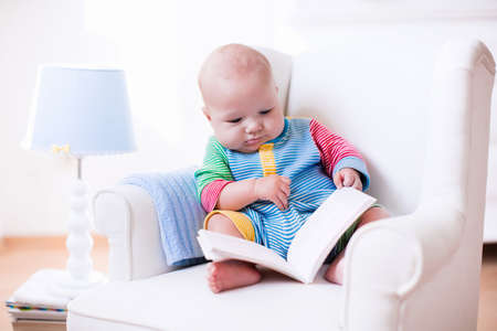 Photo for Cute funny baby boy reading a book sitting in a white chair at home. Children read books in a library seat. Nursery and playroom interior for kids. Early development and learning for young kid. - Royalty Free Image