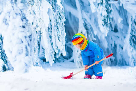 Foto de Little girl shoveling snow on home drive way. Beautiful snowy garden or front yard. Child with shovel playing outdoors in winter season. Family removing snow after blizzard. Kids play outside. - Imagen libre de derechos