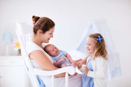 Photo pour Little sister hugging her newborn brother. Toddler kid meeting new sibling. Mother and new born baby boy relax in a white bedroom. Family with children at home. Love, trust and tenderness concept. - image libre de droit