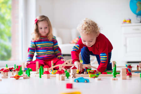 Photo pour Children playing with wooden train. Toddler kid and baby play with blocks, trains and cars. Educational toys for preschool and kindergarten child. Boy and girl build toy railroad at home or daycare. - image libre de droit
