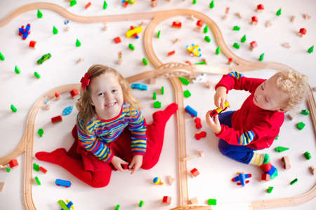 Foto de Children playing with wooden train. Toy railroad. Toddler kid and baby play with blocks, trains and cars. Educational toys for preschool and kindergarten child. View from above, kids on the floor. - Imagen libre de derechos