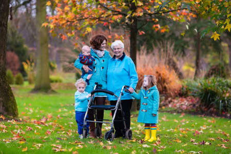 Foto de Happy senior lady with a walker or wheel chair and children. Grandmother and kids enjoying a walk in the park. Child supporting disabled grandparent. Family visit. Generations love and relationship. - Imagen libre de derechos