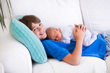 Happy laughing boy holding his sleeping newborn baby brother. Siblings with big age difference. Children playing at home on a white couch. New born child taking a nap. Kids bonding. Family love.