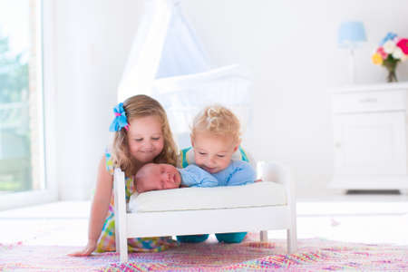 Photo pour Cute little boy and girl kissing newborn brother. Toddler kids meet new born sibling at home. Infant sleeping in toy bed in white nursery. Kids playing and bonding. Children with small age difference. - image libre de droit