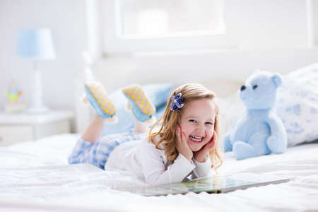 Foto de Funny happy toddler girl reading a book and playing with her toy teddy bear in bed. Kids play at home. White nursery. Child in sunny bedroom. Children read and study. Interior for baby and young kid. - Imagen libre de derechos