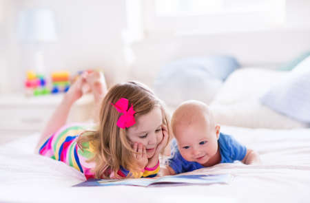 Photo pour Funny happy toddler girl reading a book and playing with newborn baby boy in bed. Kids play at home. White nursery. Child in sunny bedroom. Children read and study. Interior for baby and young kid. - image libre de droit