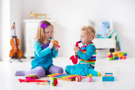 Photo for Children with music instruments. Musical education for kids. Colorful wooden art toys. Little girl and boy play music. Kid with xylophone, guitar, flute, violin. Early development for toddler and baby - Royalty Free Image