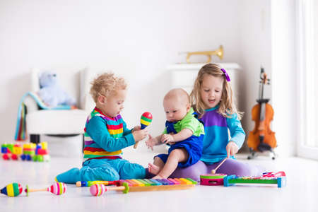 Foto de Children with music instruments. Musical education for kids. Colorful wooden art toys. Little girl and boy play music. Kid with xylophone, guitar, flute, violin. Early development for toddler and baby - Imagen libre de derechos
