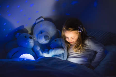Photo pour Little girl reading a book in bed. Dark bedroom with night light projecting stars on room ceiling. Kids nursery and bedding. Children read before bedtime. Toddler child playing with lamp and bear toy. - image libre de droit