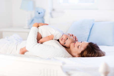Photo for Mother and child on a white bed. Mom and baby boy in diaper playing in sunny bedroom. Parent and little kid relaxing at home. Family having fun together. Bedding and textile for infant nursery. - Royalty Free Image