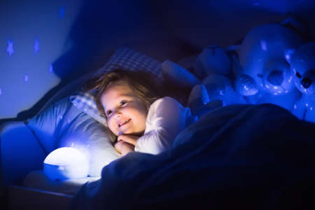 Foto de Little girl reading a book in bed. Dark bedroom with night light projecting stars on room ceiling. Kids nursery and bedding. Children read before bedtime. Toddler child playing with lamp and bear toy. - Imagen libre de derechos
