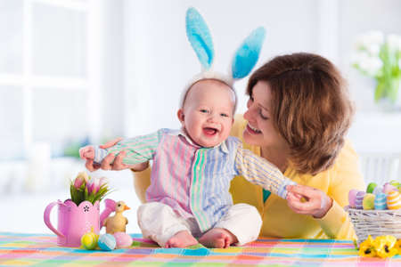 Foto de Mother and child painting colorful eggs. Mom and baby with bunny ears paint and decorate Easter egg. Parent and kid play indoors in spring. Decorated home and spring flowers. Family celebrating Easter - Imagen libre de derechos