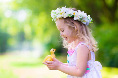 Photo pour Little girl having fun on Easter egg hunt. Kid in flower crown playing with toy duck or chicken. Children searching for eggs in the garden. Toddler kids outdoor. Happy child laughing and smiling. - image libre de droit