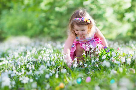 Little girl having fun on Easter egg hunt. Kids in blooming spring garden with crocus and snowdrop flowers. Children searching for eggs in the garden. Child putting colorful pastel eggs in a basket.