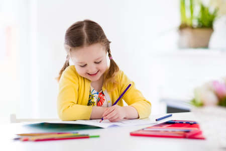 Photo for Cute little girl doing homework, reading a book, coloring pages, writing and painting. Children paint. Kids draw. Preschooler with books at home. Preschoolers learn to write and read. Creative toddler - Royalty Free Image