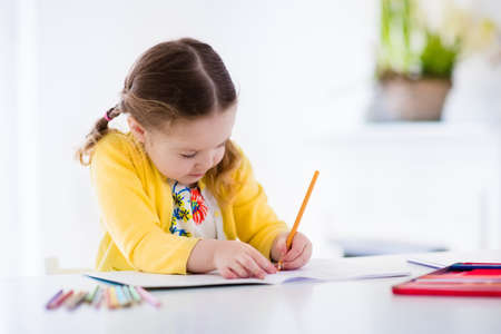 Foto de Cute little girl doing homework, reading a book, coloring pages, writing and painting. Children paint. Kids draw. Preschooler with books at home. Preschoolers learn to write and read. Creative toddler - Imagen libre de derechos