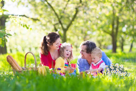 Photo pour Family with children enjoying picnic in spring garden. Parents and kids having fun eating lunch outdoors in summer park. Mother, father, son and daughter eat fruit and sandwiches on colorful blanket. - image libre de droit