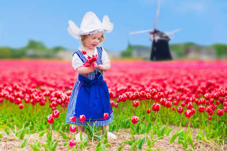 Photo for Adorable curly toddler girl wearing Dutch traditional national costume dress and hat playing in a field of blooming tulips next to a windmill in Amsterdam region, Holland, Netherlands - Royalty Free Image