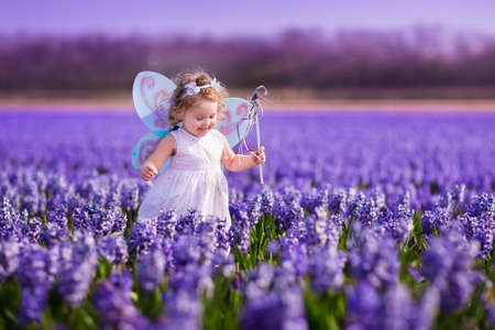 Photo pour Cute curly little girl in flower crown and fairy costume with wings and magic wand playing in hyacinth field in Holland. Child running in purple flowers. Kids gardening. Children on Easter egg hunt. - image libre de droit
