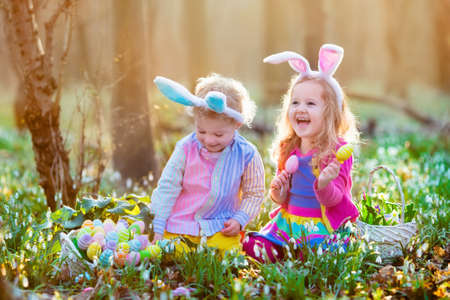 Photo for Kids on Easter egg hunt in blooming spring garden. Children with bunny ears searching for colorful eggs in snow drop flower meadow. Toddler boy and preschooler girl in rabbit costume play outdoors. - Royalty Free Image