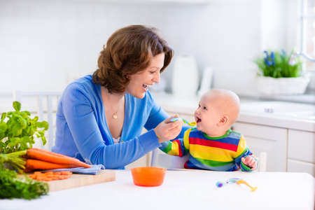 Photo for Mother feeding child. First solid food for young kid. Fresh organic carrot for vegetable lunch. Baby weaning. Mom and little boy eat vegetables. Healthy nutrition for children. Parents feed kids. - Royalty Free Image