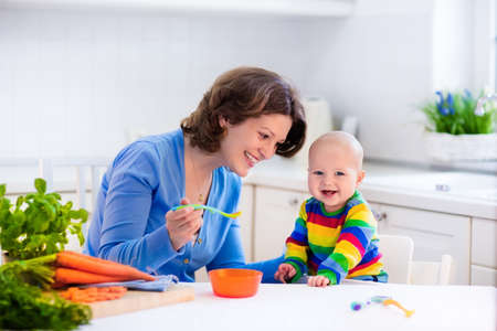 Photo pour Mother feeding child. First solid food for young kid. Fresh organic carrot for vegetable lunch. Baby weaning. Mom and little boy eat vegetables. Healthy nutrition for children. Parents feed kids. - image libre de droit