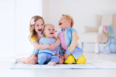 Photo pour Group of three kids playing in a white bedroom. Children play at home. Preschooler girl, toddler boy and baby in nursery. Happy little brothers and sister bonding having fun together. Siblings love. - image libre de droit