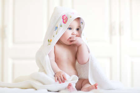 Photo pour Adorable baby girl sitting under a hooded towel after bath - image libre de droit