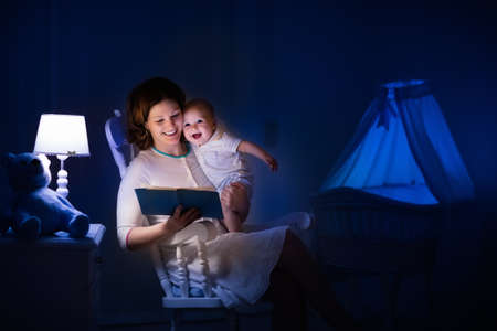 Photo for Mother and baby reading a book in dark bedroom. Mom and child read books before bed time. Family in the evening. Kids room interior with night lamp and bassinet. Parent holding infant next to crib. - Royalty Free Image