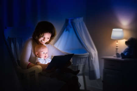 Photo pour Mother and baby reading a book in dark bedroom. Mom and child read books before bed time. Family in the evening. Kids room interior with night lamp and bassinet. Parent holding infant next to crib. - image libre de droit