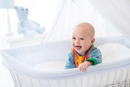 Photo pour Funny baby in white crib with canopy. Nursery interior and bedding for kids. Laughing little boy playing in moses basket. Bedroom with bassinet for young children. Happy child in colorful pajamas. - image libre de droit