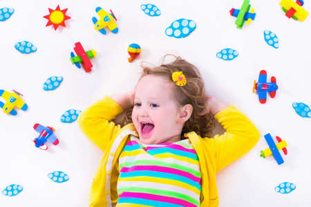 Photo pour Child playing with wooden airplanes. Preschooler kid flying around the world. Kids travelling and playing. Children at day care or kindergarten. View from above. - image libre de droit