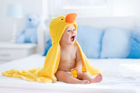 Photo for Happy laughing baby wearing yellow hooded duck towel sitting on parents bed after bath or shower. Clean dry child in bedroom. Bathing and washing of little kids. Children hygiene. Textile for infants. - Royalty Free Image