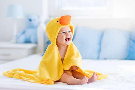 Foto de Happy laughing baby wearing yellow hooded duck towel sitting on parents bed after bath or shower. Clean dry child in bedroom. Bathing and washing of little kids. Children hygiene. Textile for infants. - Imagen libre de derechos