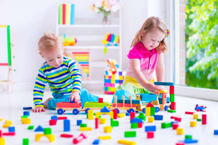Photo pour Kids play at day care. Two toddler children build tower of colorful wooden blocks. Child playing with toy train. Educational toys for preschool and kindergarten. - image libre de droit