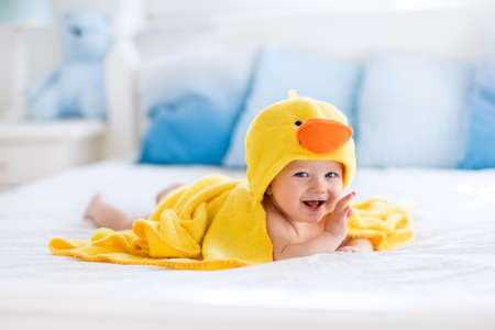 Photo pour Happy laughing baby wearing yellow hooded duck towel sitting on parents bed after bath or shower. Clean dry child in bedroom. Bathing and washing of little kids. Children hygiene. Textile for infants. - image libre de droit