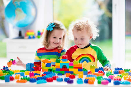 Photo pour Child playing with colorful toys. Little girl and funny curly baby boy with educational toy blocks. Children play at day care or preschool. Mess in kids room. Toddlers build a tower in kindergarten. - image libre de droit