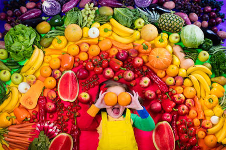 Photo for Little girl with variety of fruit and vegetable. Colorful rainbow of raw fresh fruits and vegetables. Child eating healthy snack. Vegetarian nutrition for kids. Vitamins for children. View from above. - Royalty Free Image