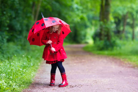 Little girl playing in rainy summer park. Child with red ladybug umbrella, waterproof coat and boots jumping in puddle and mud in the rain. Kid walking in autumn shower. Outdoor fun by any weather.