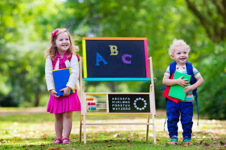 Foto de Children happy to be back to school. Preschooler girl and boy with backpack and books at black chalk board learning to write letters and read. Kids at preschool or kindergarten learn the alphabet. - Imagen libre de derechos