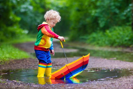 Little boy playing in rainy summer park. Child with colorful rainbow umbrella, waterproof coat and boots jumping in puddle and mud in the rain. Kid walking in autumn shower. Outdoor fun by any weather