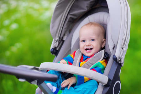 Photo pour Baby boy in warm colorful knitted jacket sitting in modern stroller on a walk in a park. Child in buggy. Little kid in a pushchair. Traveling with young kids. Transportation for family with infant. - image libre de droit