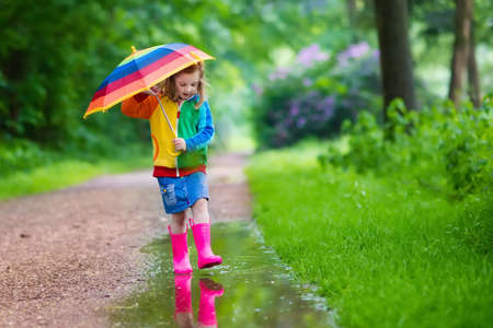 Little girl playing in rainy summer park. Child with colorful rainbow umbrella, waterproof coat, boots jumping in puddle and mud in the rain. Kid walking in autumn shower. Outdoor fun by any weather