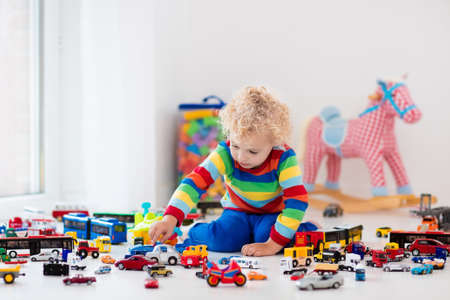 Photo pour Funny curly toddler boy playing with his model car collection on the floor. Transportation and rescue toys for children. Toy mess in child room. Many cars for little boys. Educational games for kids. - image libre de droit