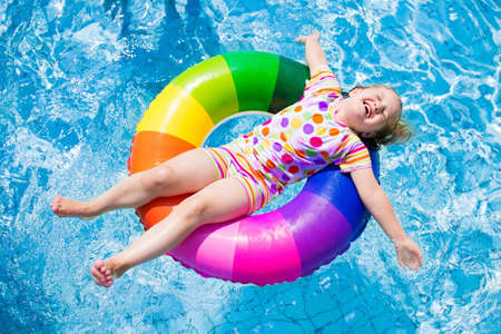 Photo for Happy little girl playing with colorful inflatable ring in outdoor swimming pool on hot summer day. Kids learn to swim. Children wearing sun protection rash guard relaxing in tropical resort - Royalty Free Image